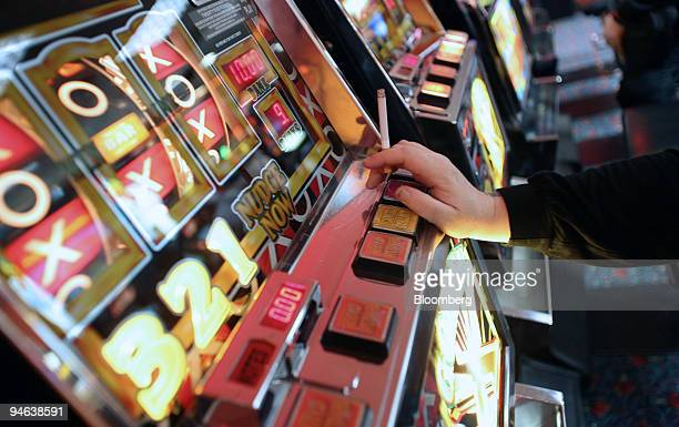 A woman smokes while playing slot machines at Beacon Bingo in Cricklewood Broadway north London on Wednesday December 13 2006 Bingo parlors once the...