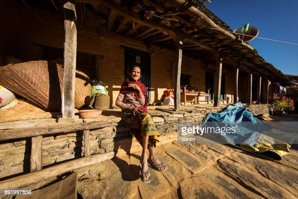 Woman smoking a cigar in front of traditional house of Himalayan Village on November 19, 2017 in HIMALAYAN VILLAGE, Nepal