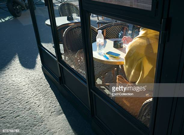 Woman smoking a cigarette at brasserie in Paris