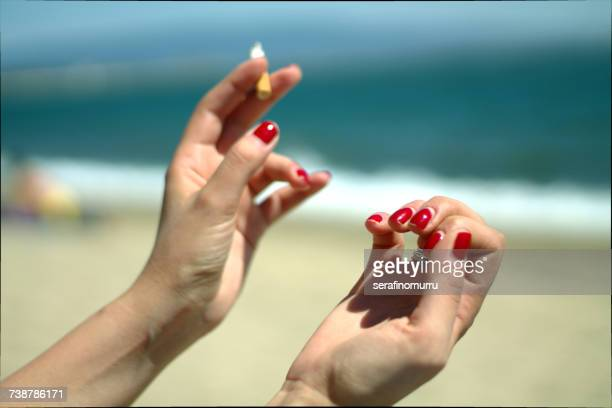 Woman smoking a cigarette on beach looking at her nails