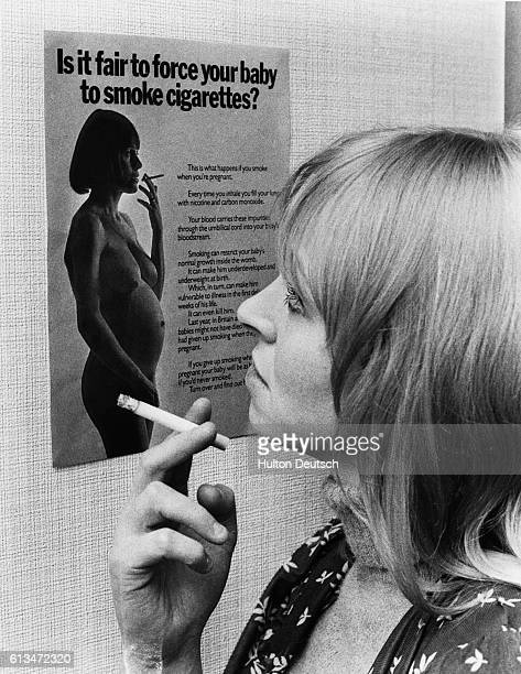 A woman smoking a cigarette pauses to read an antismoking campaign poster which warns women about the dangers of cigarettes to pregnant women and...