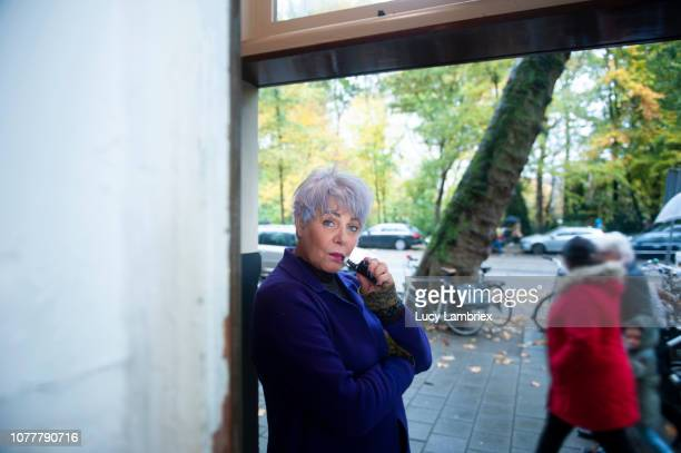 Woman smoking an electronic cigarette in front of a shop window