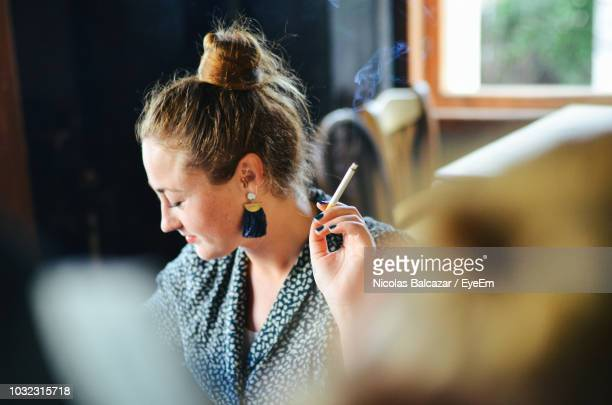 woman smoking cigarette at home - femme qui fume photos et images de collection