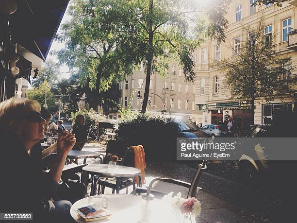 Woman Smoking Cigarette While Sitting In Cafe In City