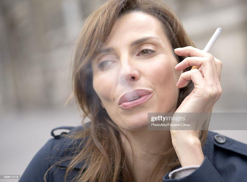 Woman smoking electronic cigarette : Stock Photo