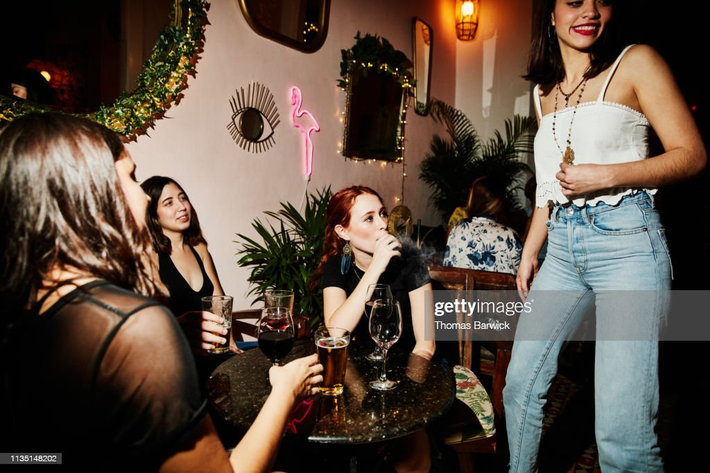 Woman smoking electronic cigarette while hanging out with friends in night club : Stock Photo