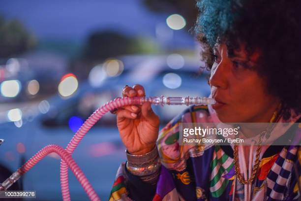 woman smoking hookah at night - chicha photos et images de collection