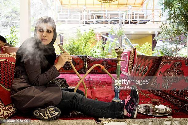 Woman smoking hookah, looking away