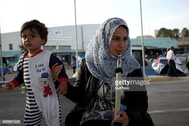 A woman smoking hookah while holding her baby Refugees and migrants stranded at the port of Piraeus in Athens Greece May 11 2016 About 2000 people...