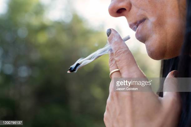 woman smoking marijuana preroll joint - medical cannabis stock pictures, royalty-free photos & images