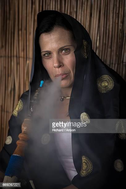 Woman smoking nargile (traditional water pipe)