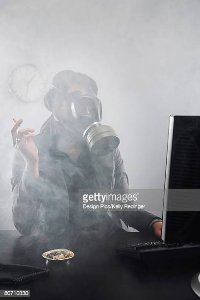 Woman smoking with gas mask