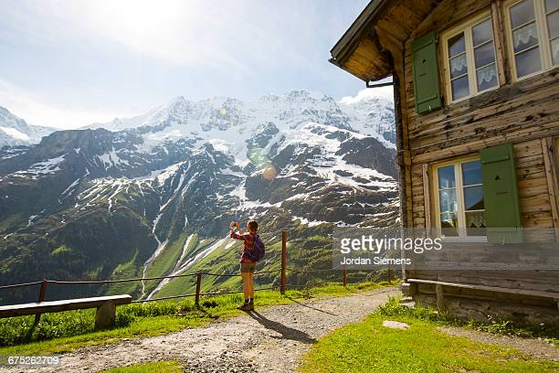 A woman snapping a photo of the Alps.