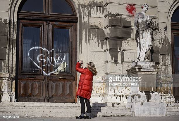 A woman snaps a picture of the Grand Theatre de Geneve opera house on December 20 2015 in Geneva after it was vandalised during a demonstration the...