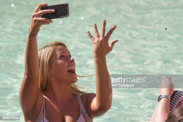 A woman snaps a selfie as she throws a coin in the Trevi Fountain on June 21 2017 in Rome / AFP PHOTO / Tiziana FABI