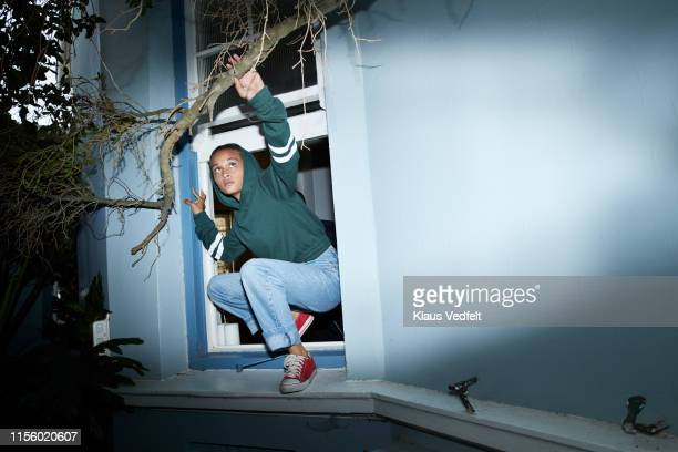 woman sneaking out of house window - dishonesty stock pictures, royalty-free photos & images
