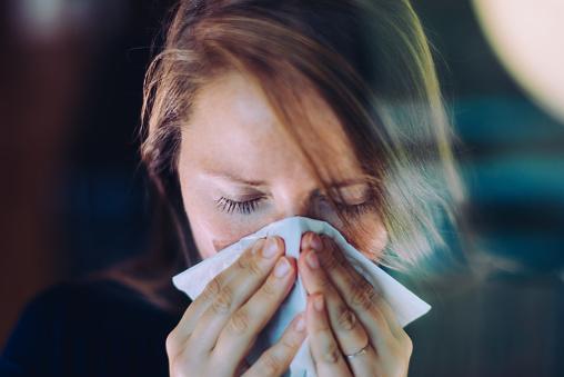 Woman sneezing behind a window. - gettyimageskorea