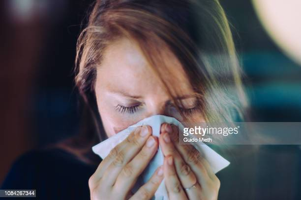 woman sneezing behind a window. - pneumonia stock pictures, royalty-free photos & images