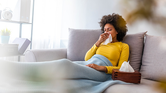 Woman sneezing in a tissue in the living room. 1149518691