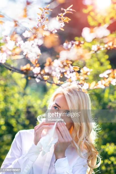 woman sneezing in the blossoming garden - immune system stock pictures, royalty-free photos & images