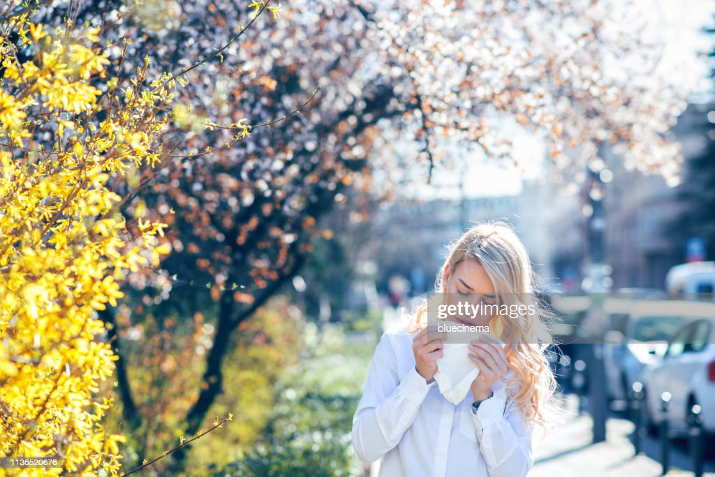 Vrouw niezen in de bloeiende tuin : Stockfoto