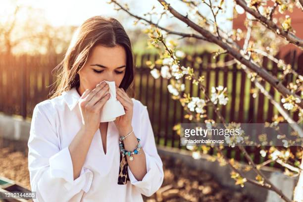 woman sneezing in the blossoming garden - cold virus stock pictures, royalty-free photos & images