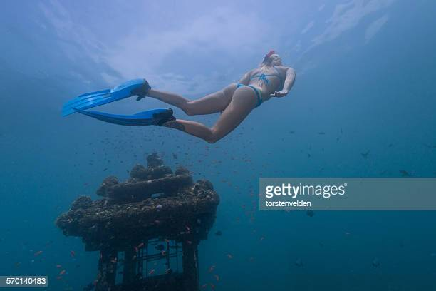 Woman snorkeling by a sunken temple, Bali, Indonesia