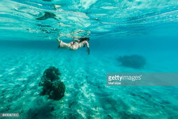 Woman snorkeling in clear water in Bora Bora.