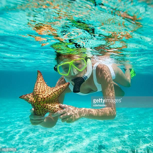 Frau Schnorcheln mit Seestern in der Karibik