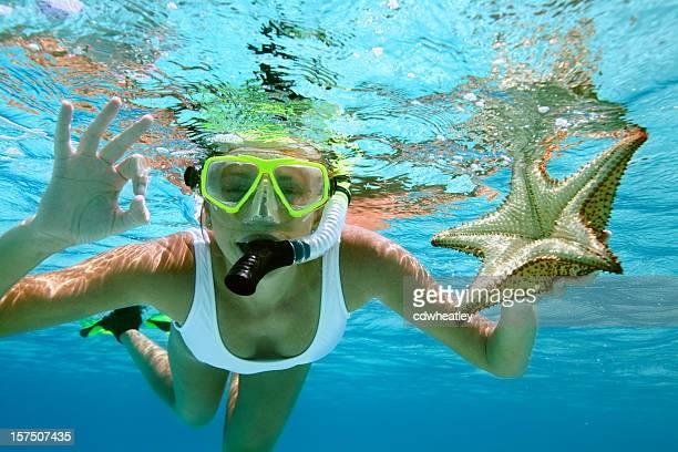Femme plongée avec masque et tuba avec une étoile de mer