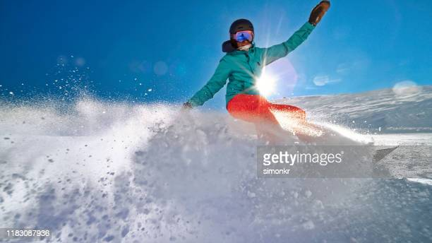 woman snowboarding on mountain - ski wear stock pictures, royalty-free photos & images