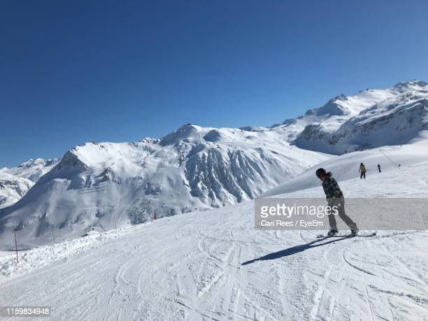 woman snowboarding on snowcapped mountain against clear sky - cari stock pictures, royalty-free photos & images