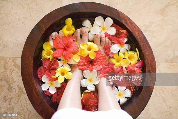 woman soaking feet in footbath with flowers, saipan  - saipan stock pictures, royalty-free photos & images