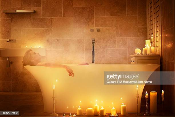 Woman soaking in bathtub with candles