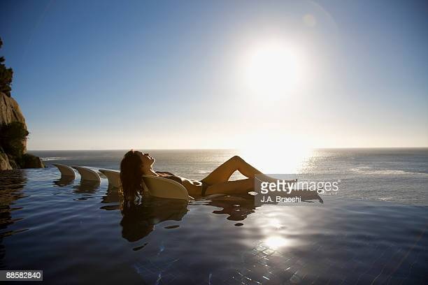 Woman soaking in infinity pool near ocean