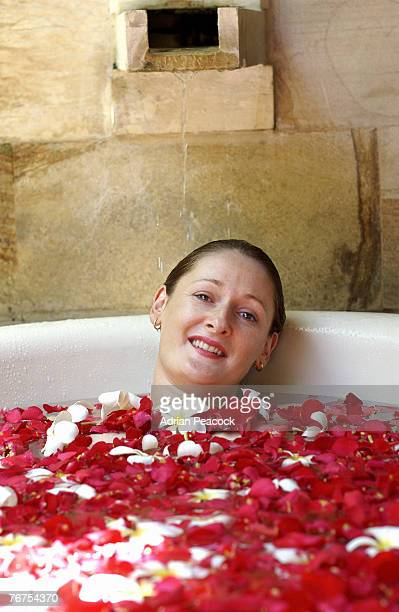 Woman soaking in rose petal bath