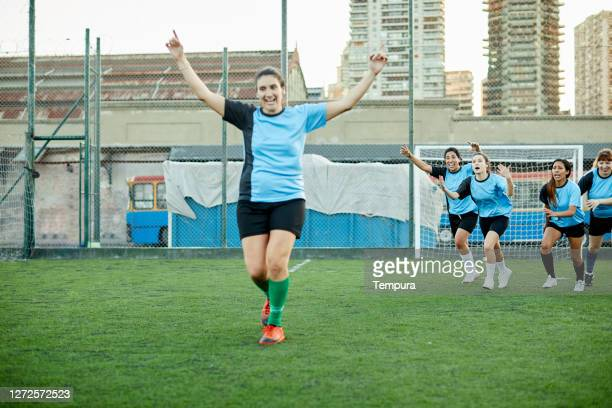 a woman soccer player celebrating a goal. - soccer competition stock pictures, royalty-free photos & images
