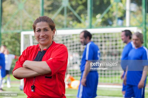 woman soccer referee looks at the camera and smiles during the match - female umpire stock pictures, royalty-free photos & images