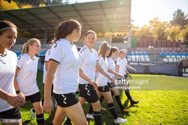 equipo de fútbol femenino caminando en los campos de entrenamiento - fútbol femenino fotografías e imágenes de stock