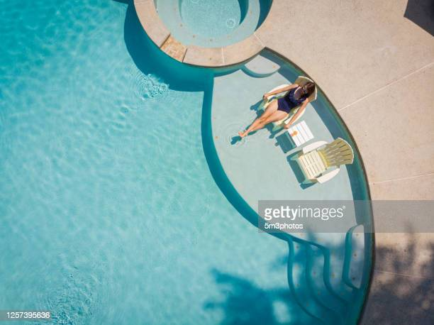 woman social distancing at home in pool - ティール色 ストックフォトと画像