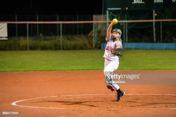 woman softball pitcher throwing the ball - baseball pitcher stock pictures, royalty-free photos & images