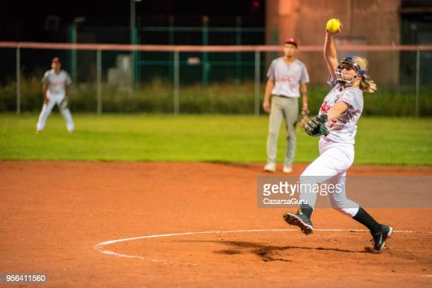woman softball pitcher throwing the ball - softball stock pictures, royalty-free photos & images