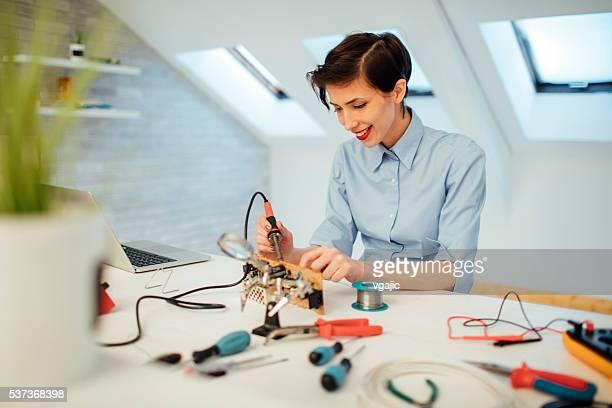 Una mujer de soldadura en placa de circuito en su oficina.