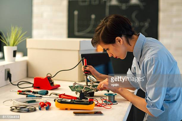Woman Soldering a circuit board in her tech office.