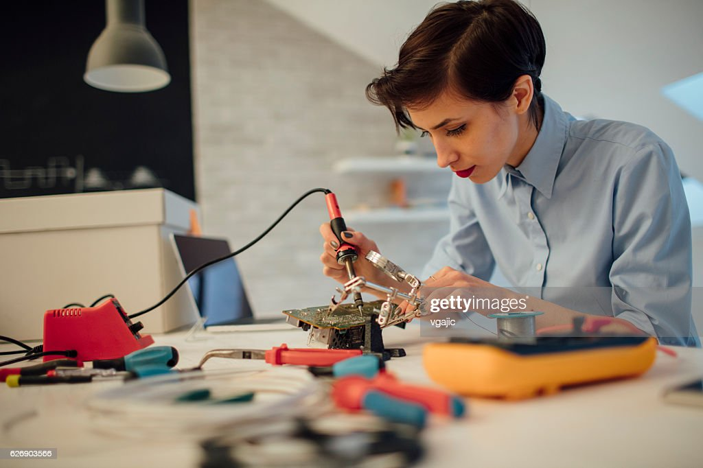 Woman Soldering a circuit board in her tech office. : Stock Photo