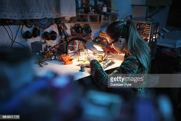 woman soldering in workshop - leanincollection stock pictures, royalty-free photos & images