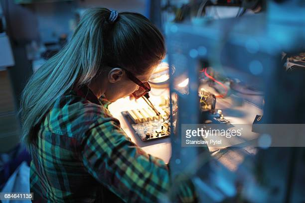 Woman soldering in workshop