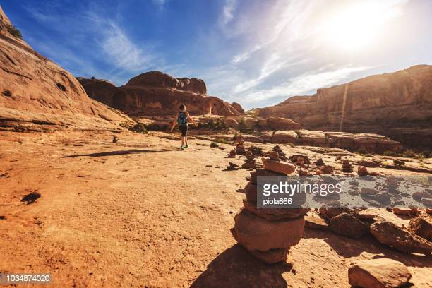 woman solo hiking in the colorado plateau: corona arch - cairns stock pictures, royalty-free photos & images