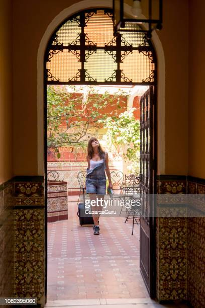 Woman Solo Traveler Checking In in Characteristic Hostel, Spain