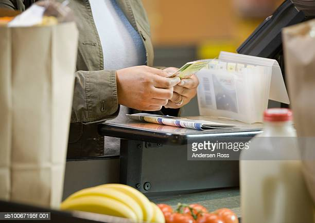 woman sorting coupons at supermarket, close-up, mid section - vale - fotografias e filmes do acervo